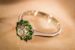 Anello in oro bianco 18 kt con diamante centrale e contorno di gemme di tzavorite.