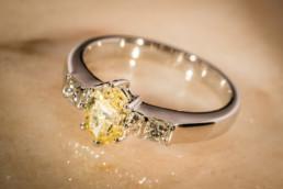 Anello in oro bianco 18 kt con diamanti laterali carré ed un raro e prezioso diamante centrale giallo.