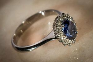 Anello in oro bianco 18kt con zaffiro ovale centrale e contorno di diamanti.
