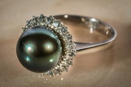 Anello in oro bianco 18 kt, con contorno di diamanti e pregiatissima perla tahitiana grigio verde centrale.