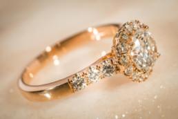 Anello in oro rosa 18 kt, con diamante centrale e contorno di diamanti.