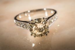 Anello in oro bianco 18 kt, diamanti laterali e al centro un unico diamante.