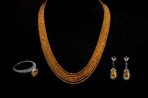 Collana di granato giallo abbinata ad orecchini ed anello in zaffiro giallo, diamanti, zaffiri blu montati su oro bianco.